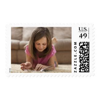 USA, Utah, Lehi, Girl (10-11) lying on rug, Postage Stamp