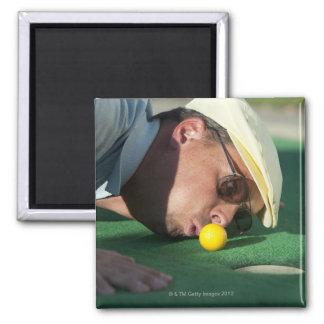 USA, Utah, Orem, Man blowing air to push golf Magnet