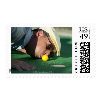 USA, Utah, Orem, Man blowing air to push golf Stamp