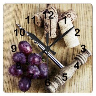Uvas, corchos de la botella de vino y sacacorchos reloj cuadrado
