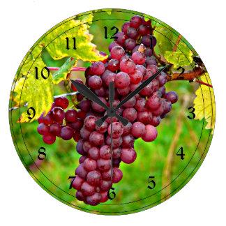 Uvas rojas en la vid relojes