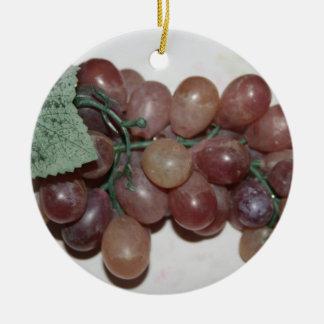 Uvas rojas, plástico, en fondo pálido adorno navideño redondo de cerámica