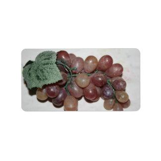 Uvas rojas, plástico, en fondo pálido etiquetas de dirección