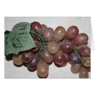 Uvas rojas, plástico, en fondo pálido felicitación
