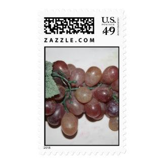 Uvas rojas, plástico, en fondo pálido franqueo