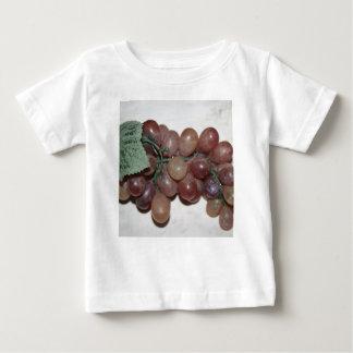 Uvas rojas, plástico, en fondo pálido playera de bebé