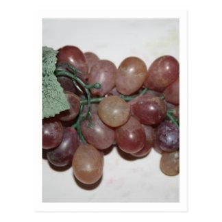 Uvas rojas, plástico, en fondo pálido postal
