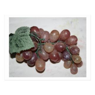 Uvas rojas, plástico, en fondo pálido postales