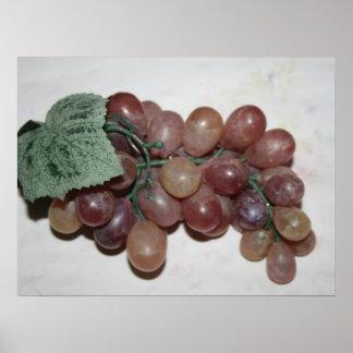 Uvas rojas, plástico, en fondo pálido póster