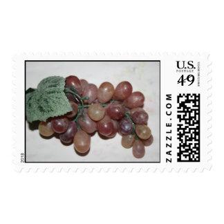 Uvas rojas, plástico, en fondo pálido sellos
