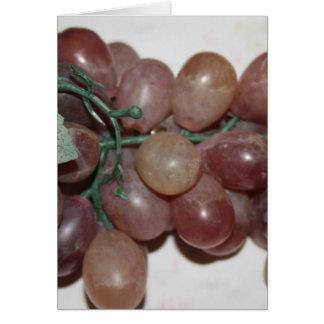 Uvas rojas, plástico, en fondo pálido felicitaciones