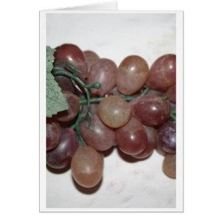Uvas rojas, plástico, en fondo pálido felicitacion