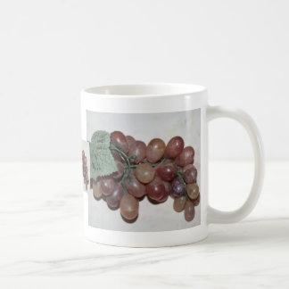 Uvas rojas plástico en fondo pálido taza de café