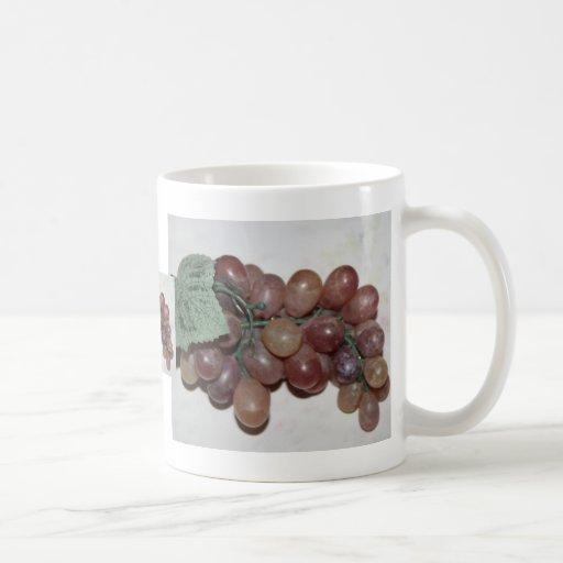 Uvas rojas, plástico, en fondo pálido taza básica blanca