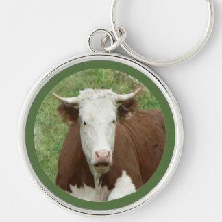 Vaca de mirada divertida en llavero de la hierba
