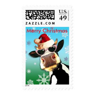 Vaca divertida del navidad que lleva el gorra de sello postal
