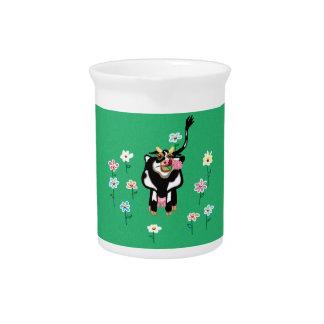 Vaca en un campo de la hierba y de las flores jarron
