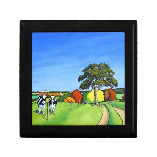 Vacas blancos y negros por el carril del país joyero cuadrado pequeño