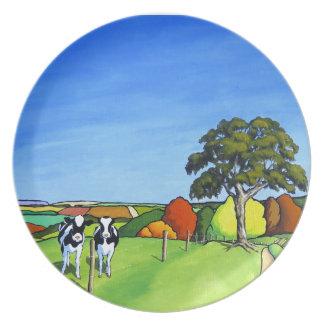 Vacas blancos y negros por el carril del país plato