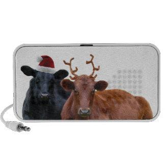 Vacas del día de fiesta del navidad en el gorra y  altavoces de viaje