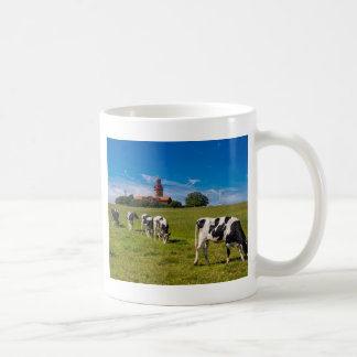 Vacas en un prado con el faro taza de café