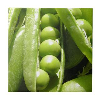 Vainas de guisante verde abiertas frescas en luz azulejo cerámica