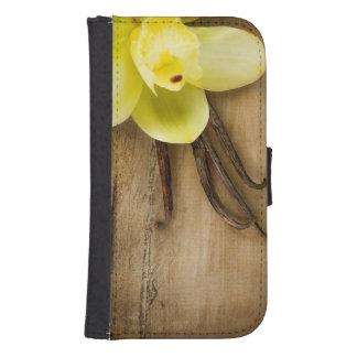 Vainas y flor de la vainilla sobre fondo de madera billeteras para teléfono