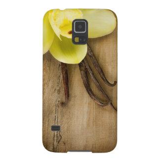 Vainas y flor de la vainilla sobre fondo de madera funda galaxy s5