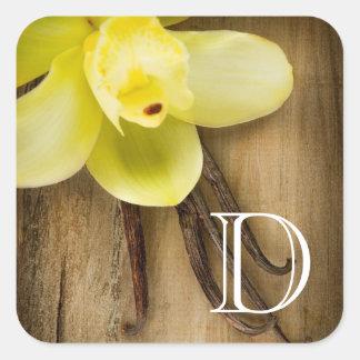 Vainas y flor de la vainilla sobre fondo de madera pegatina cuadrada