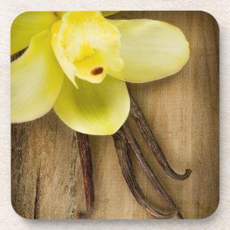 Vainas y flor de la vainilla sobre fondo de madera posavasos