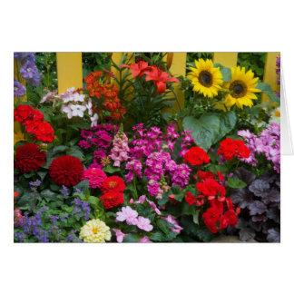 Valla de estacas amarilla con el jardín de flores  tarjeta de felicitación