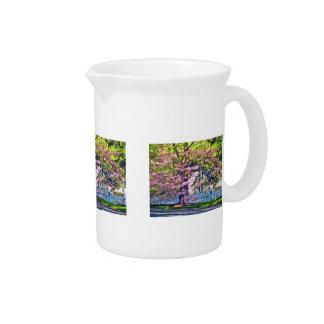 Valla de estacas blanca por los árboles jarras de beber