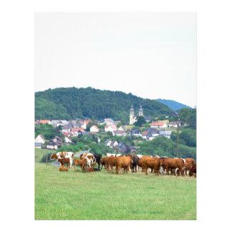 Valle con las casas y las vacas de ciudad en prado plantillas de membrete