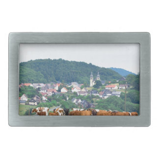 Valley with town houses and cows in meadow belt buckle