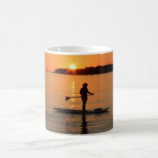 Vaquera del tablero de paleta en la puesta del sol taza de café