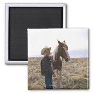 Vaquera joven auténtica en gama con el caballo imán cuadrado