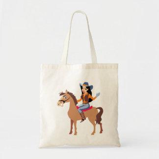 Vaquera que monta una bolsa de asas del caballo