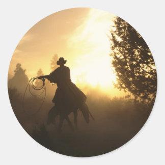 Vaquero con el lazo en puesta del sol pegatinas redondas