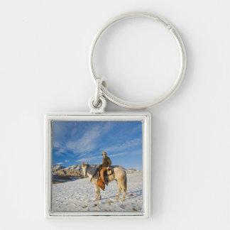 Vaquero en su caballo en la nieve 2 llaveros personalizados