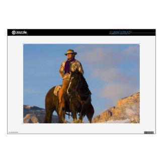 Vaquero en su caballo en la nieve calcomanía para portátil