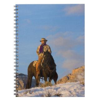 Vaquero en su caballo en la nieve spiral notebook