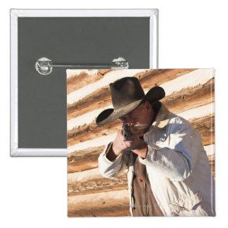 Vaquero que apunta su arma, haciendo una pausa un pin cuadrado