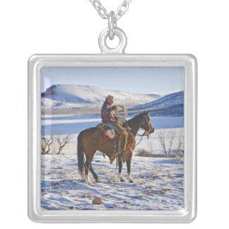 Vaquero que monta un caballo en la gama en colgante cuadrado