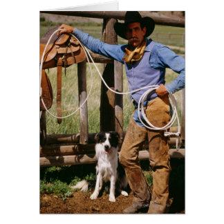 Vaquero que presenta con el lazo y el perro casero tarjeton