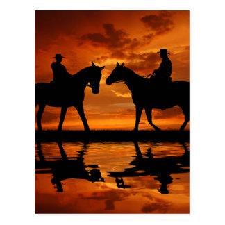 Vaqueros del montar a caballo en puesta del sol tarjetas postales