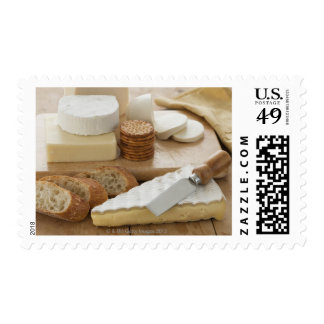 Various cheeses and bread on table postage