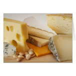 Various cheeses on chopping board greeting card