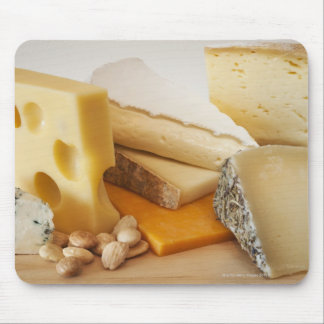 Various cheeses on chopping board mouse pad