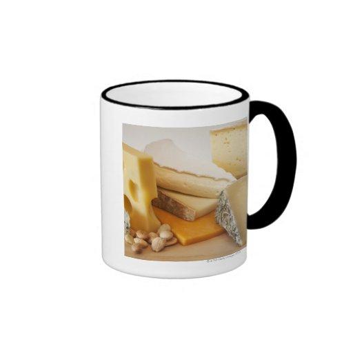 Various cheeses on chopping board ringer coffee mug