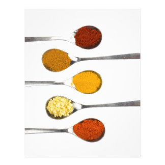 Various seasoning spices on metal spoons letterhead